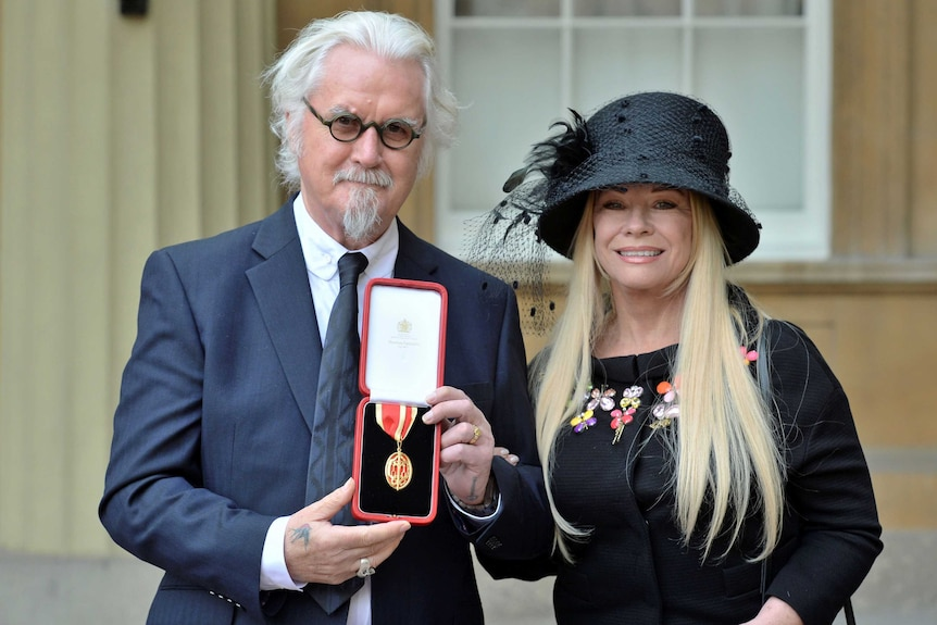 Billy Connolly and his wife Pamela Stephenson pose after he was knighted by Britain's Prince William.