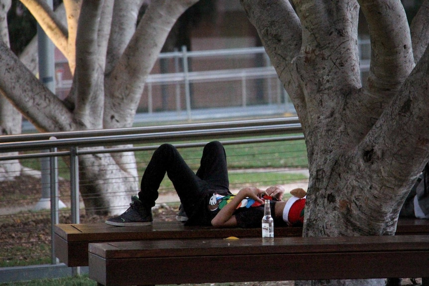 A new year's reveller rests under a tree at South Bank, Brisbane.