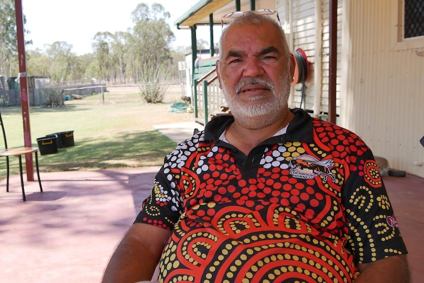 A man, wearing a bright shirt with Aboriginal artworks, sits on a patio with bushland in the background.