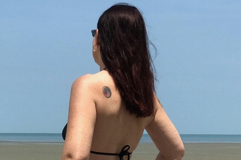 Noriel who is an escort in Cairns wearing a swim suit and looking out to sea with her back to camera.