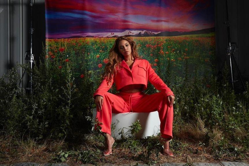 Beyonce sits on a stool in a coral tracksuit in a garden in front of a landscape backdrop