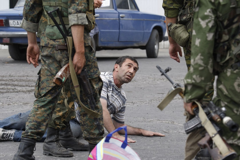 Russian soldiers detain a man who carried a weapon in his car at a checkpoint in Gori, South Ossetia