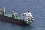 An aerial photo of a cargo ship on water.