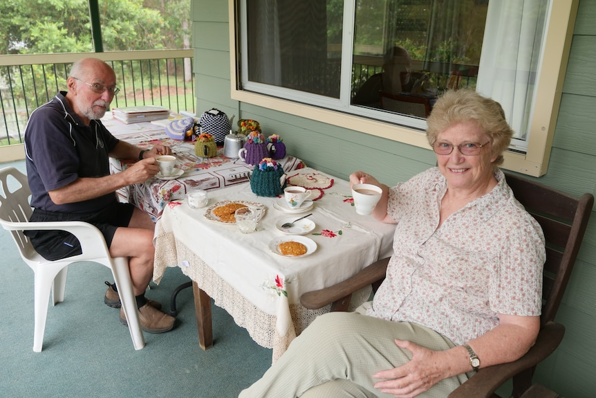 An older man and woman sit on a deck drinking a cup of tea, with a teapot on the table.