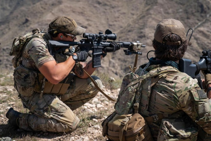 Two US Special forces soldiers with military rifles ready to fire at ISIS forces in Afghanistan.