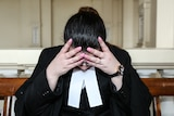 A stressed out lawyer in her robes holding her head in her hands.