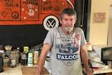 Chris Hooper, grey t-shirt, shorts, toaster, kettle, kitchen stuff behind, kombi van orange painted on wall behind.