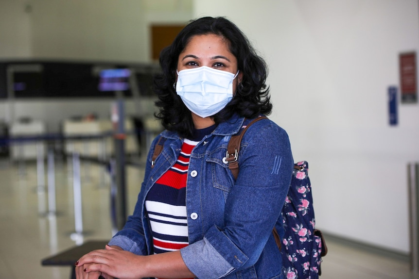 A lady with a denim jacket and a mask smiles at the camera