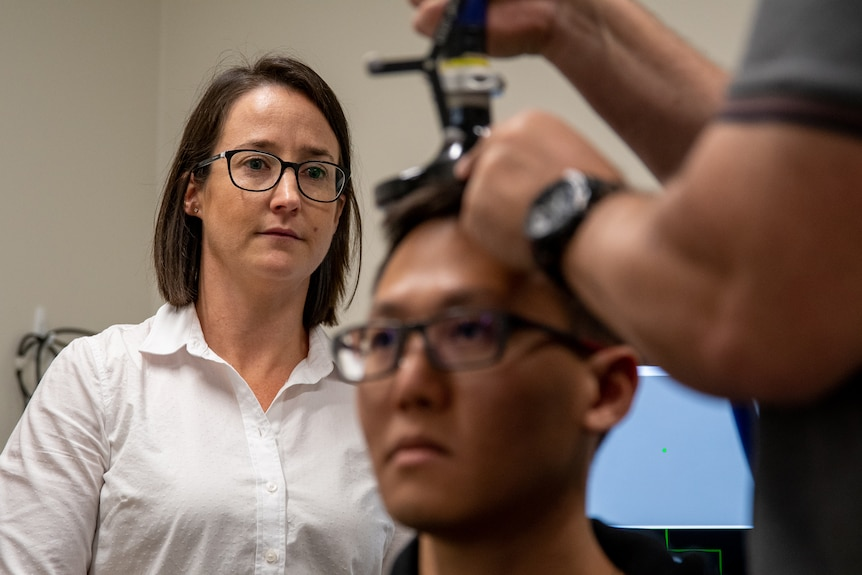 Woman with dark hair and glasses watching medical scan conducted on young man in lab