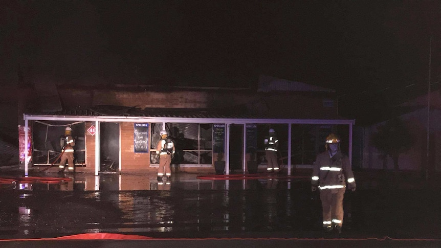 Firefighters outside a gutted building.