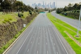 The empty city-bound lanes of the Eastern Freeway, viewed from an overpass, with the CBD skyline visible ahead.