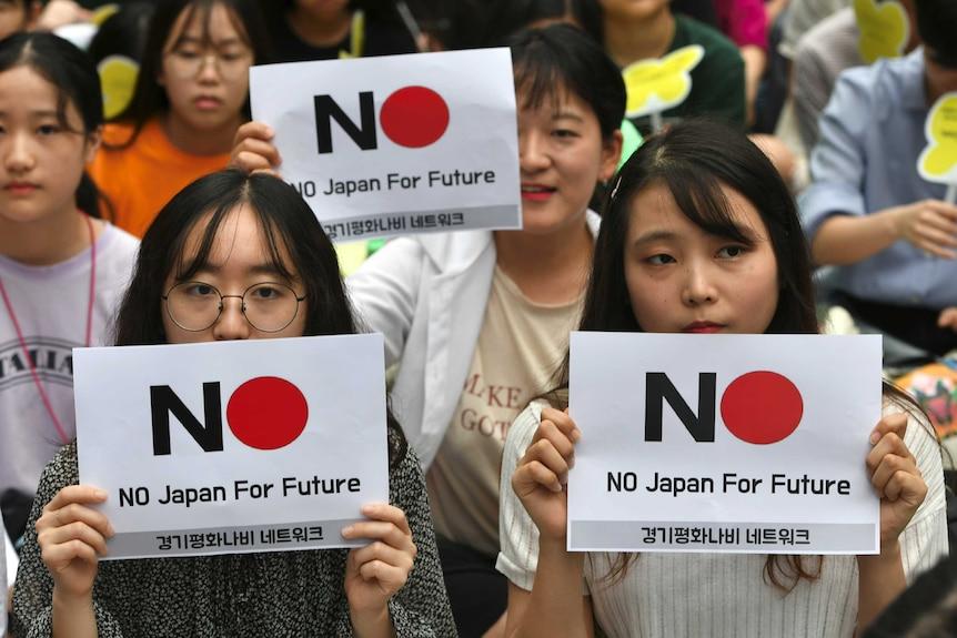 Women hold anti-Japanese signage reading 'No Japan for future.'