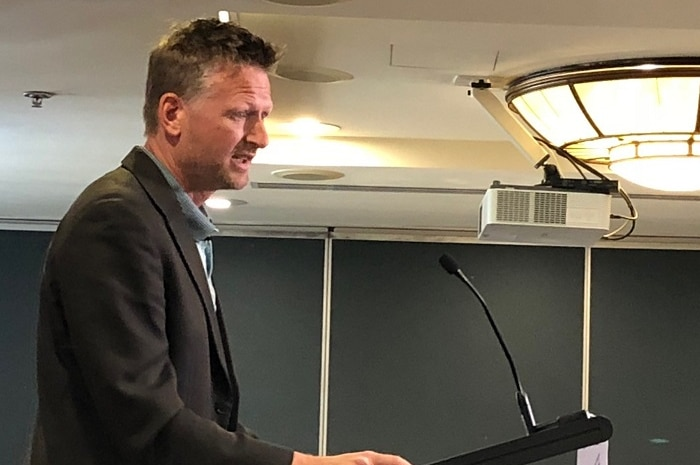 Author and former activist Mark Lynas on a podium addressing a farm conference.