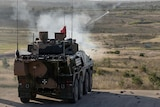 A military vehicle similar to a tank fires a shot out across the horizon, with smoke rising from the cannon.