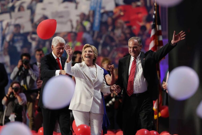 Hillary Clinton walks through falling balloons with running mate Tim Kaine