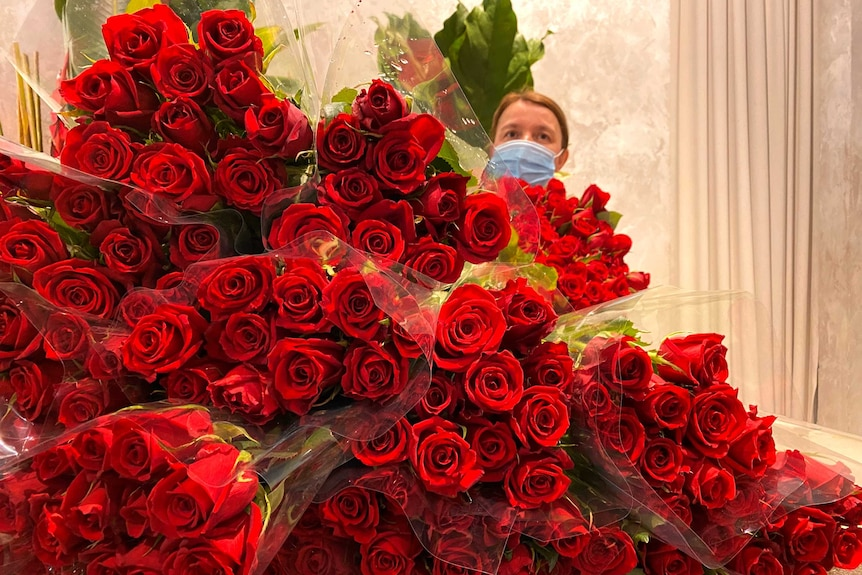 A woman is standing behind hundreds of red roses