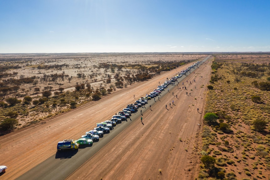An aerial shot of a straight, dusty road in a desert with a line of cars travelling along it.