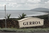 A brick wall on top of a hill overlooking Gerroa beach on a cloudy day. There are large letters spelling out GERROA on the sign.