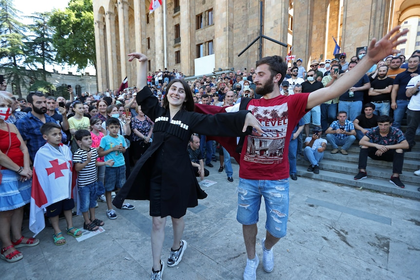 A man and woman dance ringed by people outside of a building.
