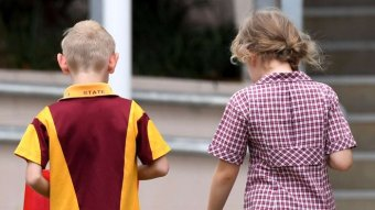 A boy and girl in school uniform from behind.