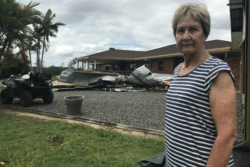 Kay Dorman looking bleak with her damaged home and a pile of corrugated iron behind her.