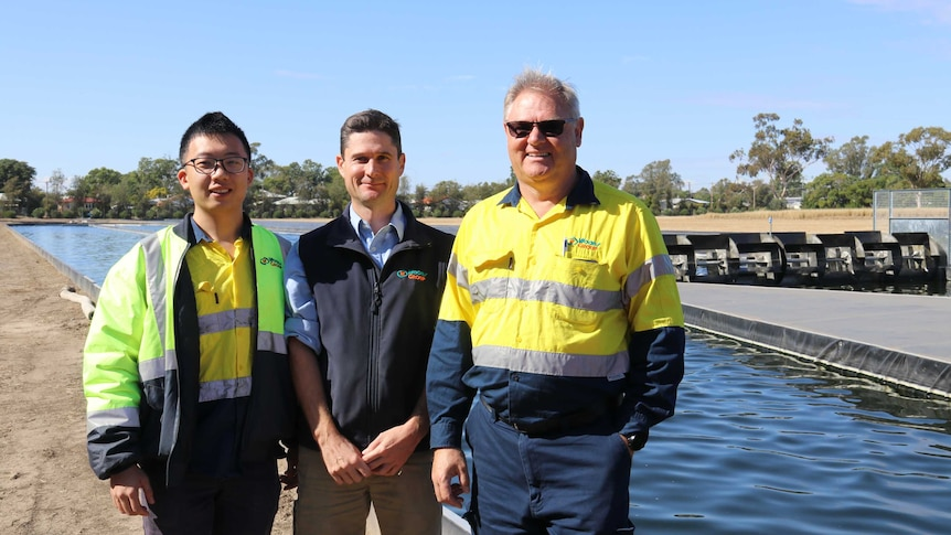 Kai Chen, Tom Woods and Steve Strutt standing in front of one of the algae ponds at Goondiwindi, May 2020.
