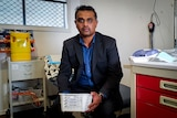 Dr Ranatunga sits in his medical practice, holding a plastic box with COVID vaccines inside