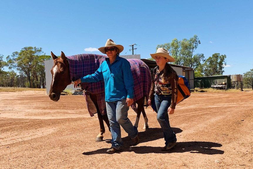 Jacky O'Dell and her 12-year-old daughter at their property Toarbee, in western Queensland walking in the yard with their horse.