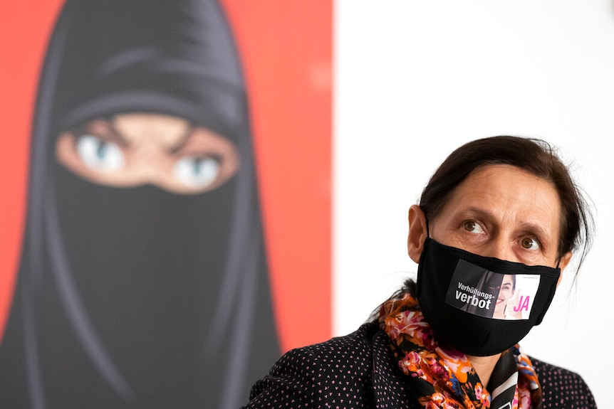 A woman wearing a face mask sits in front of a sign advocating for the banning of face coverings.