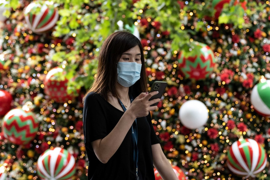 A woman in a face mask texts as she walks past a Christmas treet