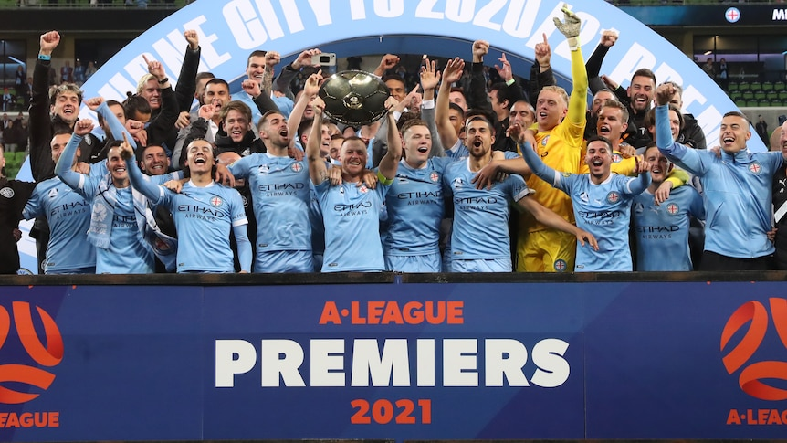 Melbourne City players celebrate while holding up the A-League premiership plate.