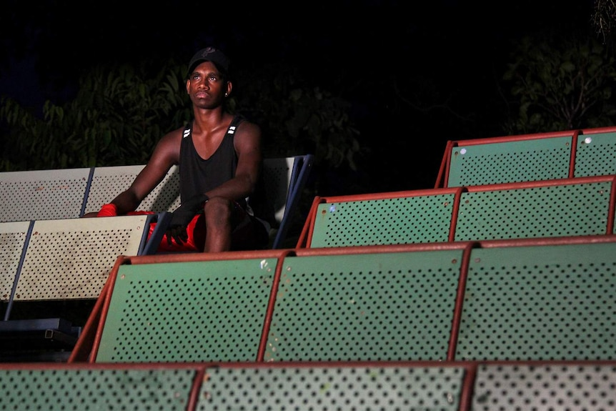 A photo of Indigenous boxer Stephen Tipungwuti sitting in the stands at the Bush Church Boxing Club.
