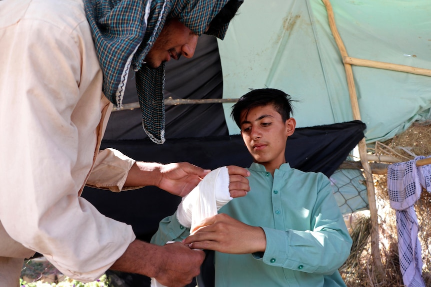 An Afghan youth receives medical care after being injured in fighting between the Taliban and Afghan security forces