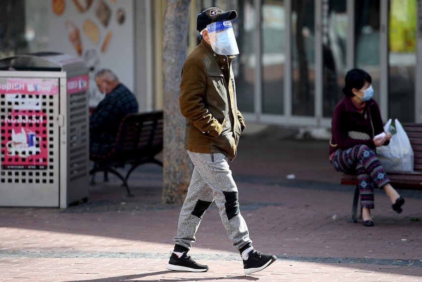 A person walks down a street wearing a face mask, a plastic face shield and a cap. Their hands are in their jacket pockets