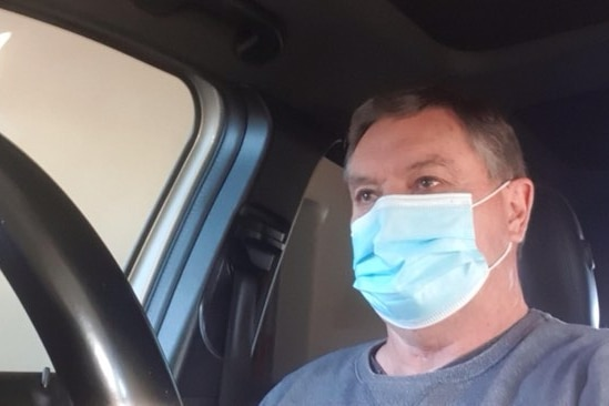 A man in a mask stares off camera, part of a car steering wheel in the frame