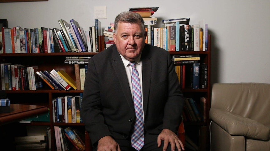 Craig Kelly sits on a chair in front of a full bookshelf. He wears a suit and has his hands on his knees as he looks into camera