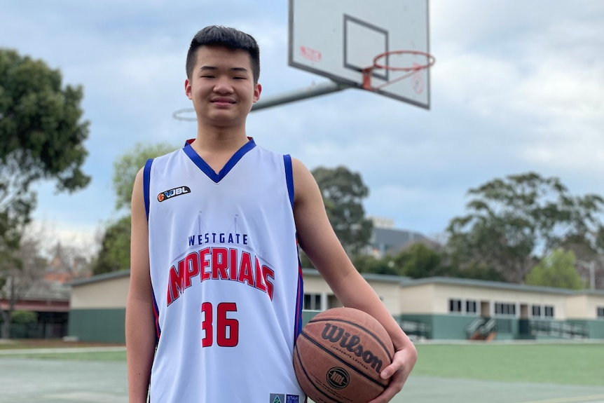 An Asian boy in a white basketball jersey with blue trims, number 36, stands in front of basketball hoop holding a basketball.