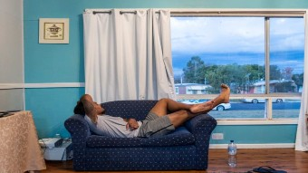 A man sleeping on a small couch.