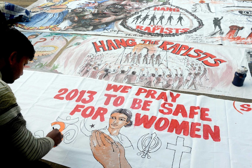 A bystander writes on a banner supporting the hanging of the rapists.