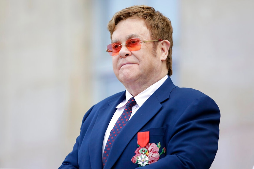 Elton John wearing a suit and a medal on his suit jacket.