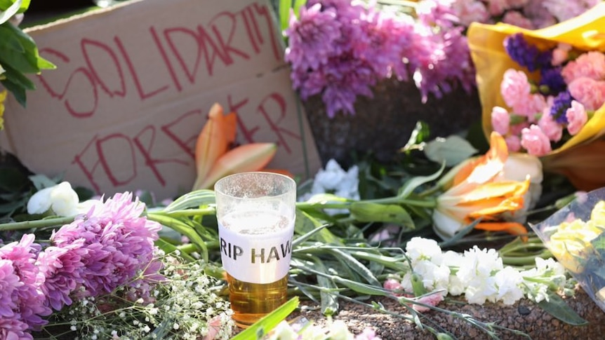 A pint of beer with the label RIP HAWKE is left in a throng of flowers on the Opera House steps.