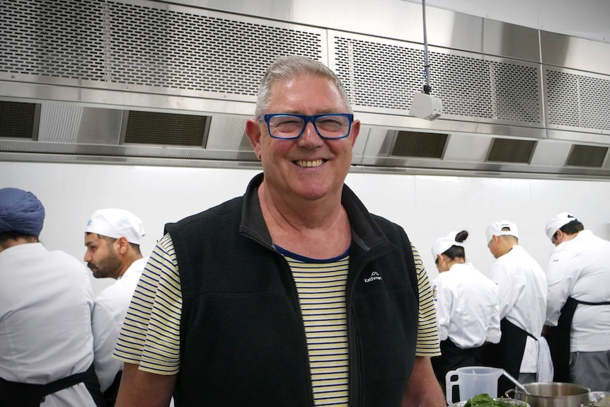A man wearing a jacket and glasses smiles while standing in a commercial kitchen
