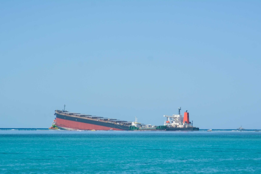 A cargo ship is seen with its aft submerged under sea water.