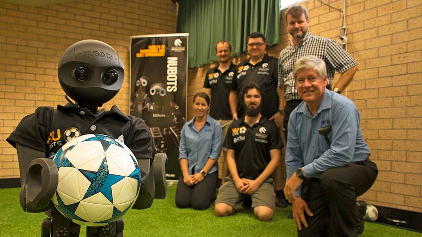 Robot holding a soccer ball in far left corner. Students and professors in the background look towards the camera.