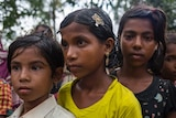 3 children waiting in line to get the relief from the Bangladesh Red Crescent Society.