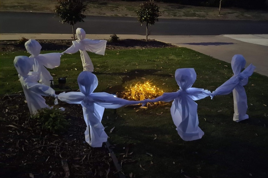 Ghosts made of white fabric standing around a campfire in a front garden