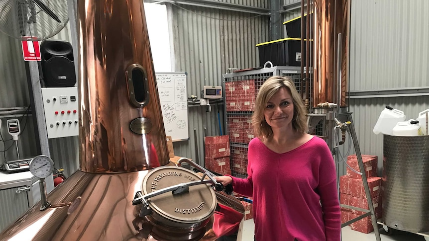A woman smiles as she leans on a large copper still inside a large shed.