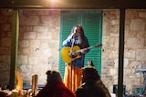 Mary G, playing guitar and singing for delegates at Coolgardie as part of a WA Aboriginal languages conference in June 2016.