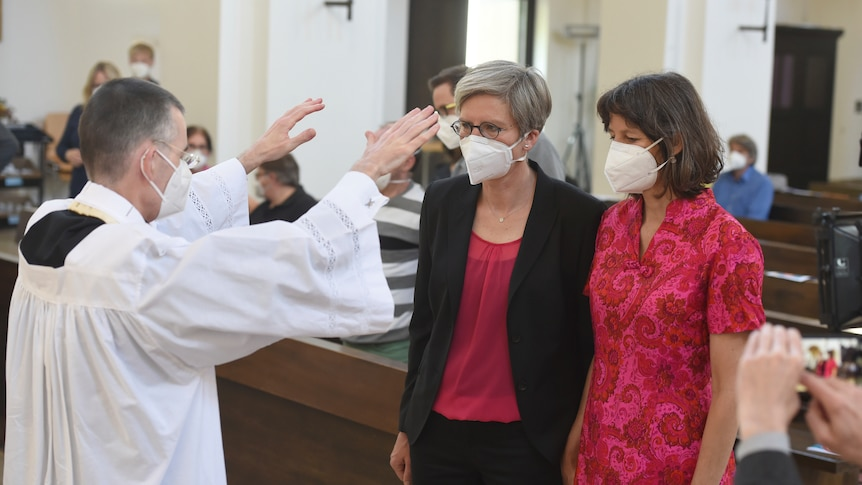 A priest raises his hands over two women in a church, all three are wearing face masks over their noses and mouths.