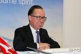 Qantas CEO Alan Joyce rests his arms on a Qantas plane model.